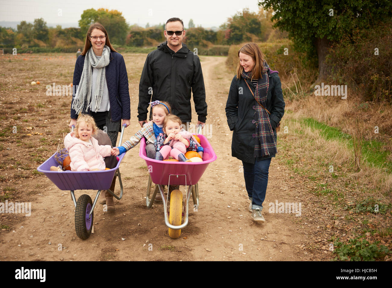 Portrait of parents pushing three girls in wheelbarrows along pumpkin field Stock Photo