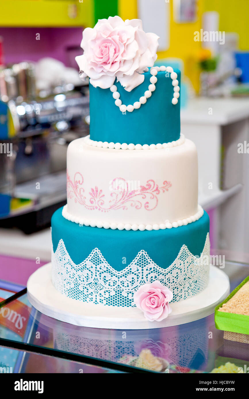 Three tier Wedding cake with blue icing lace and pearls - Stock Image