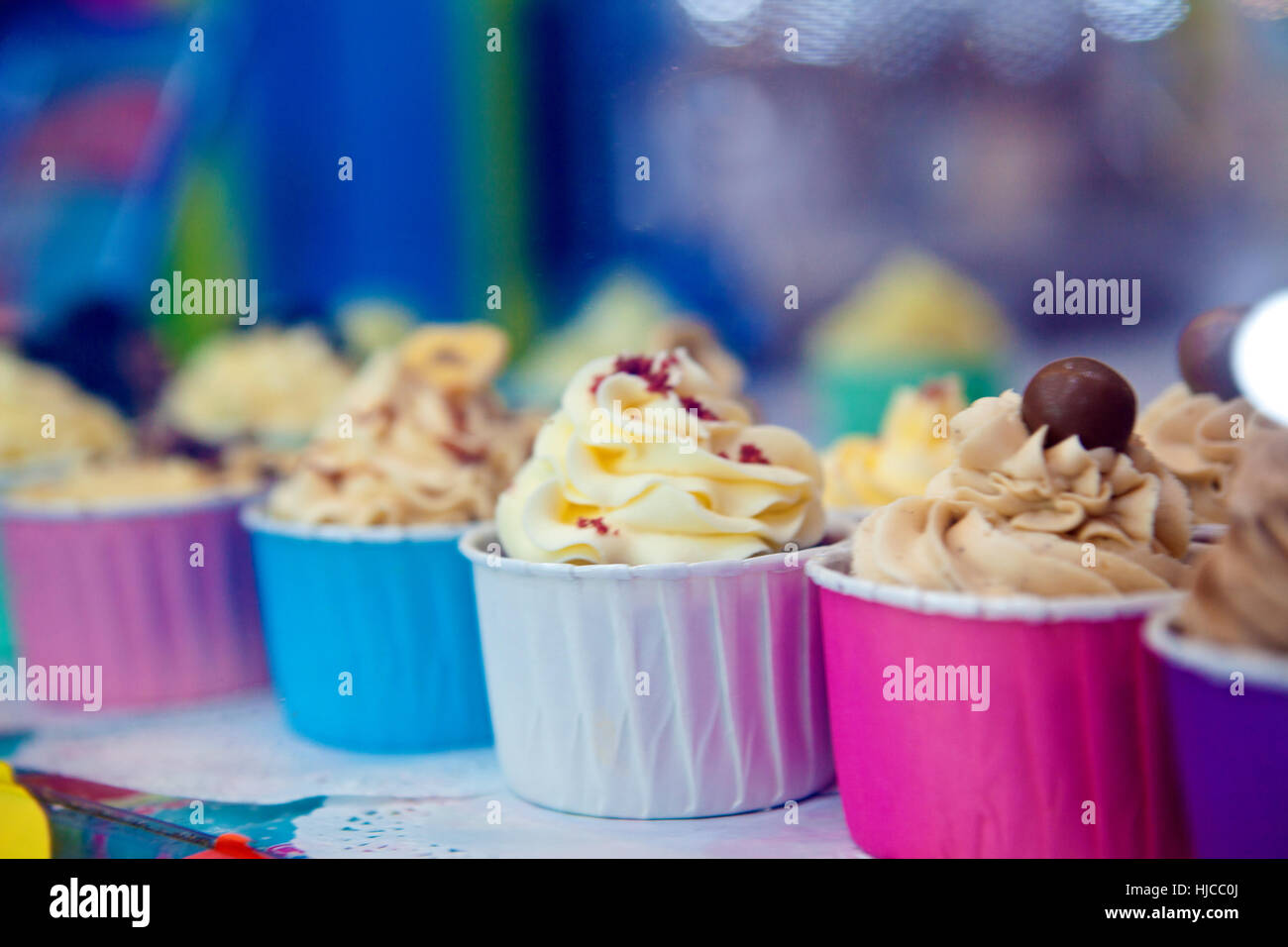 Row of colourful cupcakes with icing swirls in shop window - Stock Image
