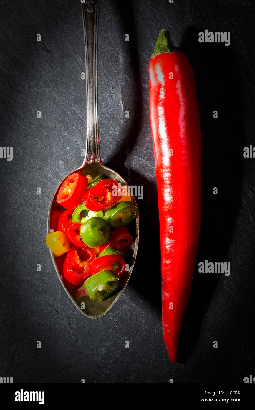 Red hot pepper peperoni whole and chopped on a spoon and on black slate background. - Stock Image