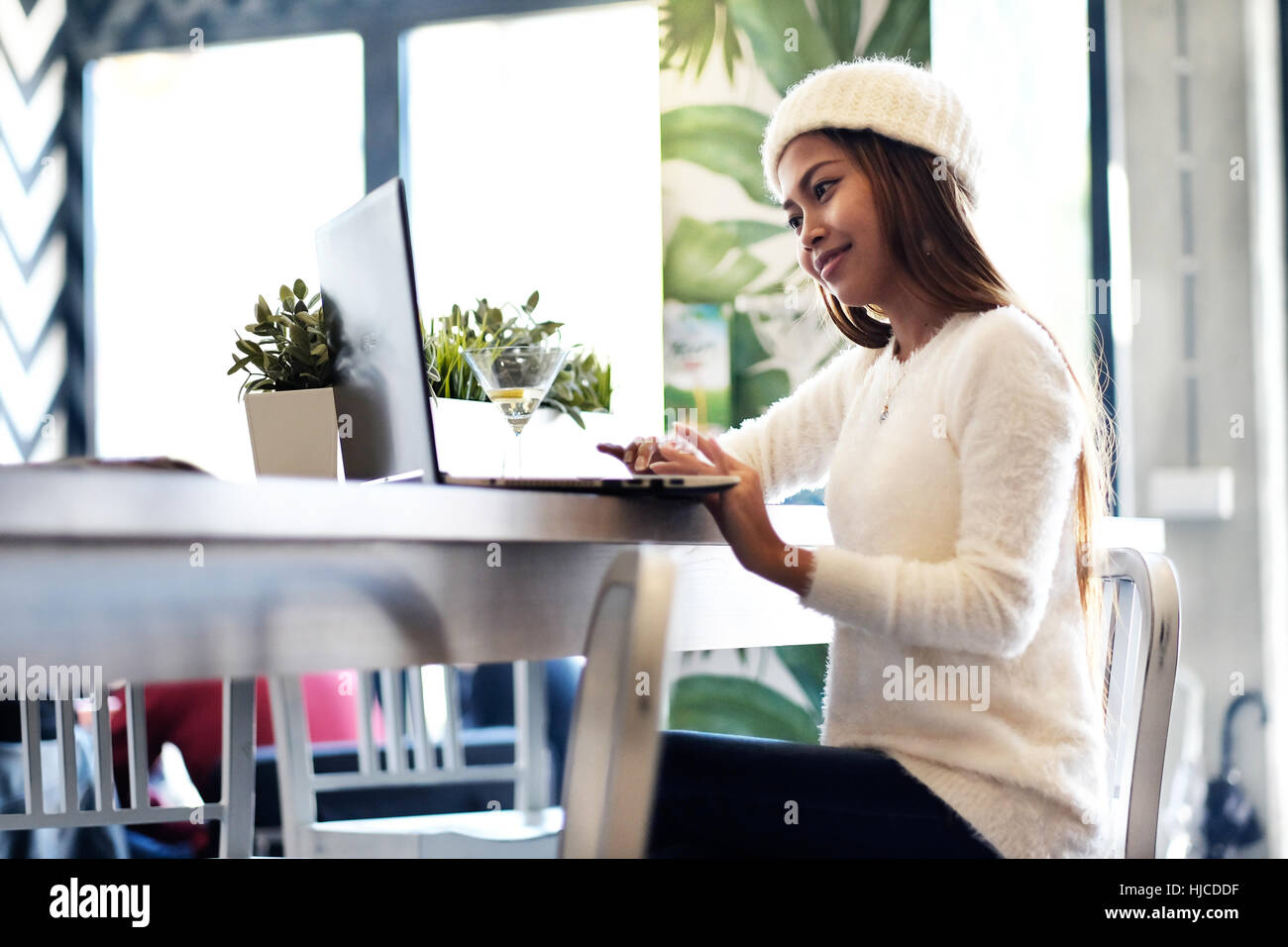 Beautiful girl networking in a café with laptop computer - Stock Image