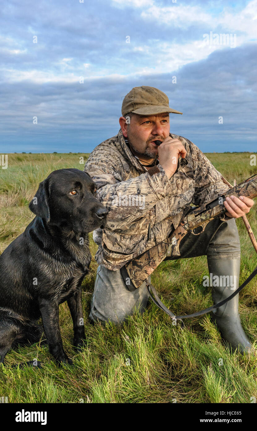 81b17f7356306 A wildfowler, or duck hunter, with his dog on the Lincolnshire marsh  blowing into