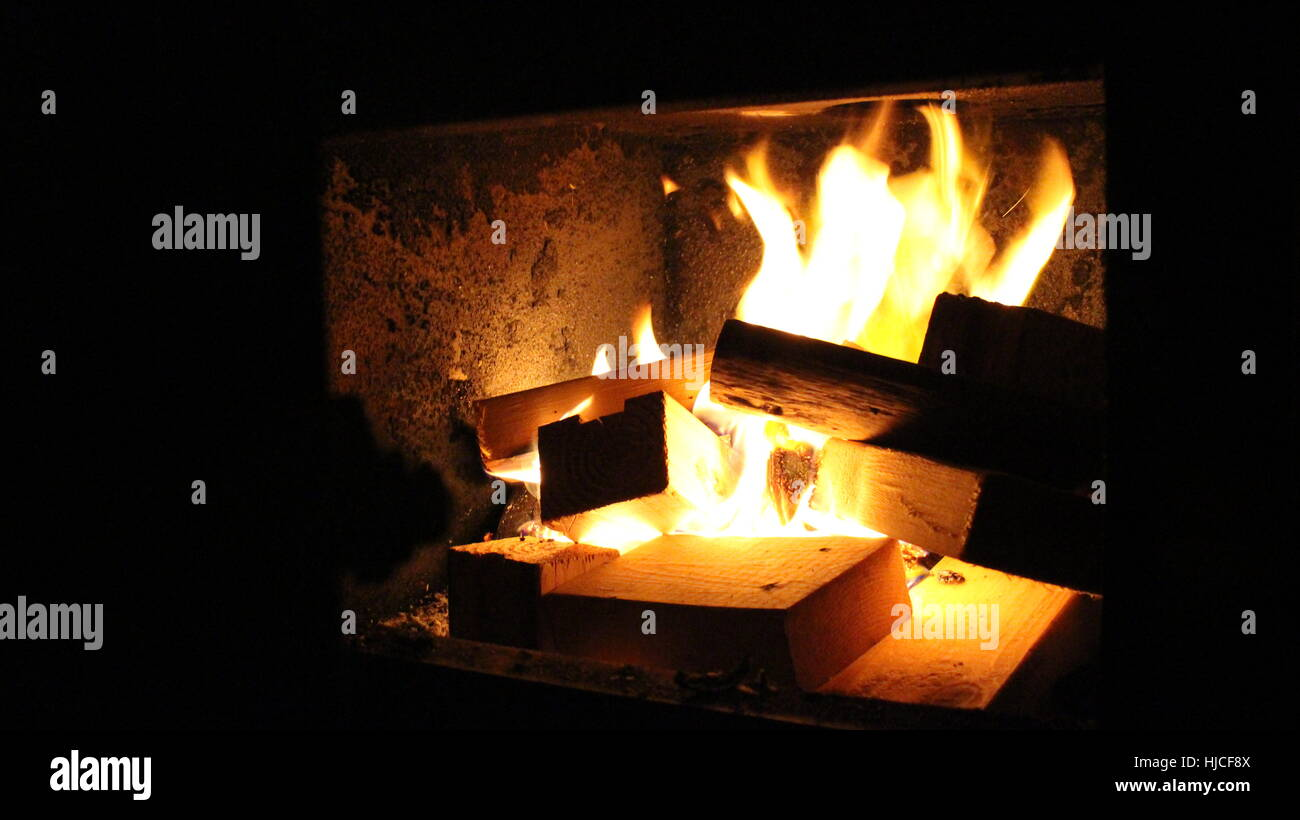 A warming fire in an old fashion stove - Stock Image