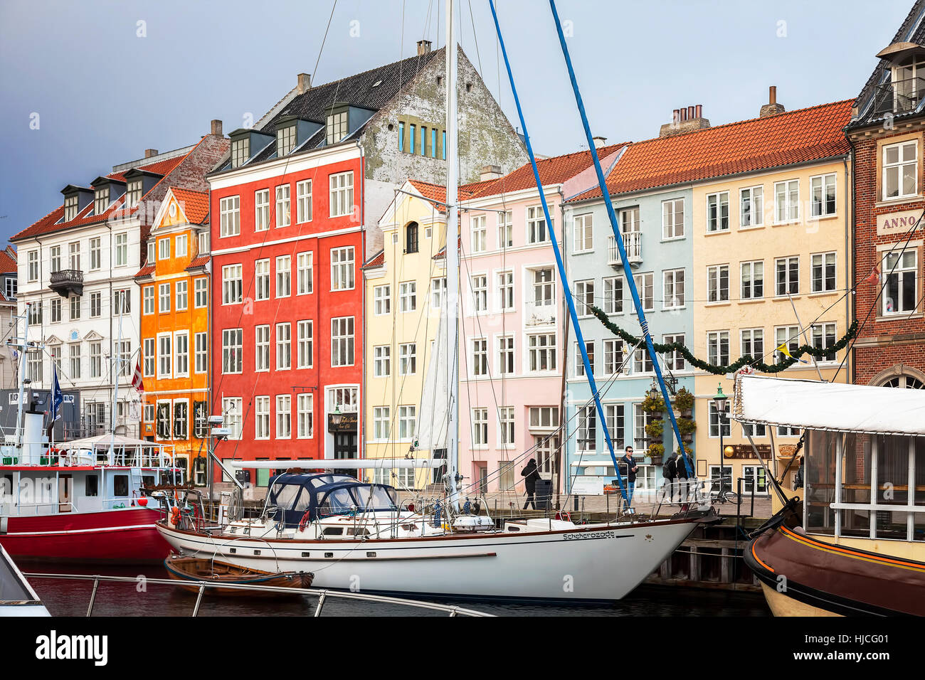 Ships and colourful buildings in the Nyhavn area of Copenhagen. - Stock Image
