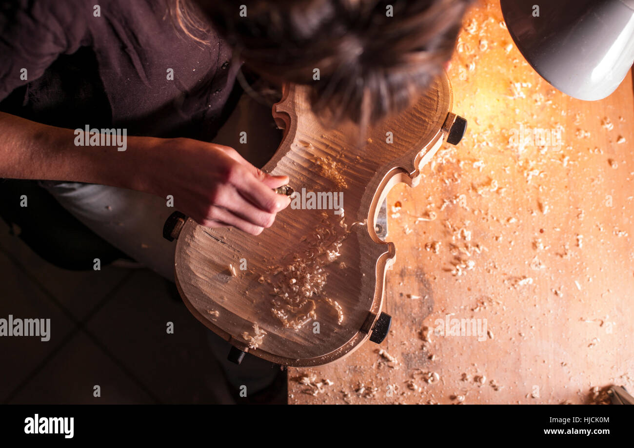 Woman violin maker, luthier, at work in her laboratory in Cremona, Italy - Stock Image
