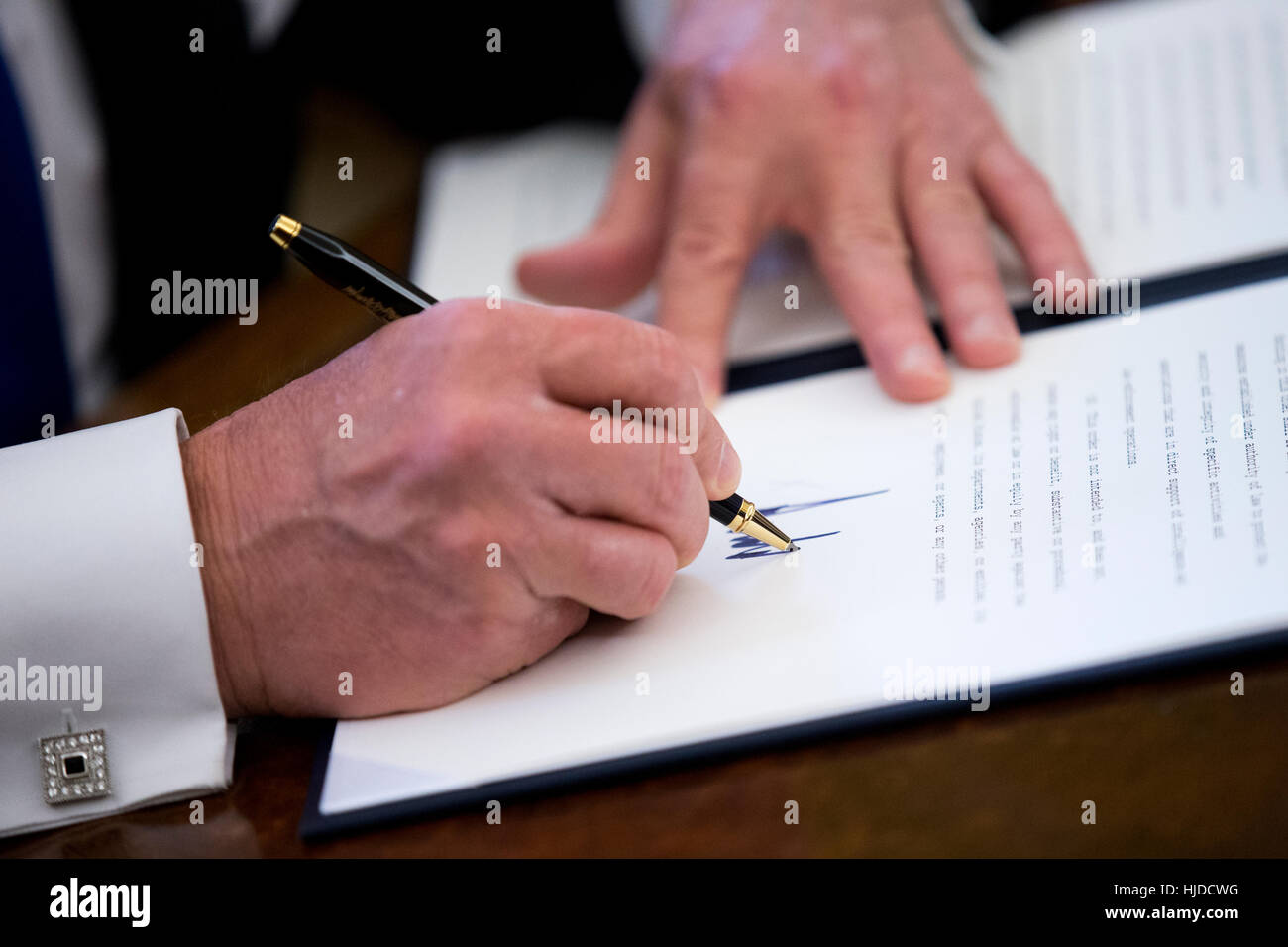 Washington, USA. 24th Jan, 2017. US President Donald Trump signs one of five executive orders related to the oil Stock Photo