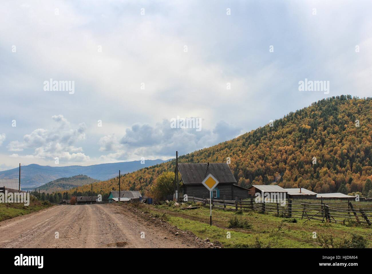 Rural road passing through the village in the mountains. Autumn mountain landscape. - Stock Image