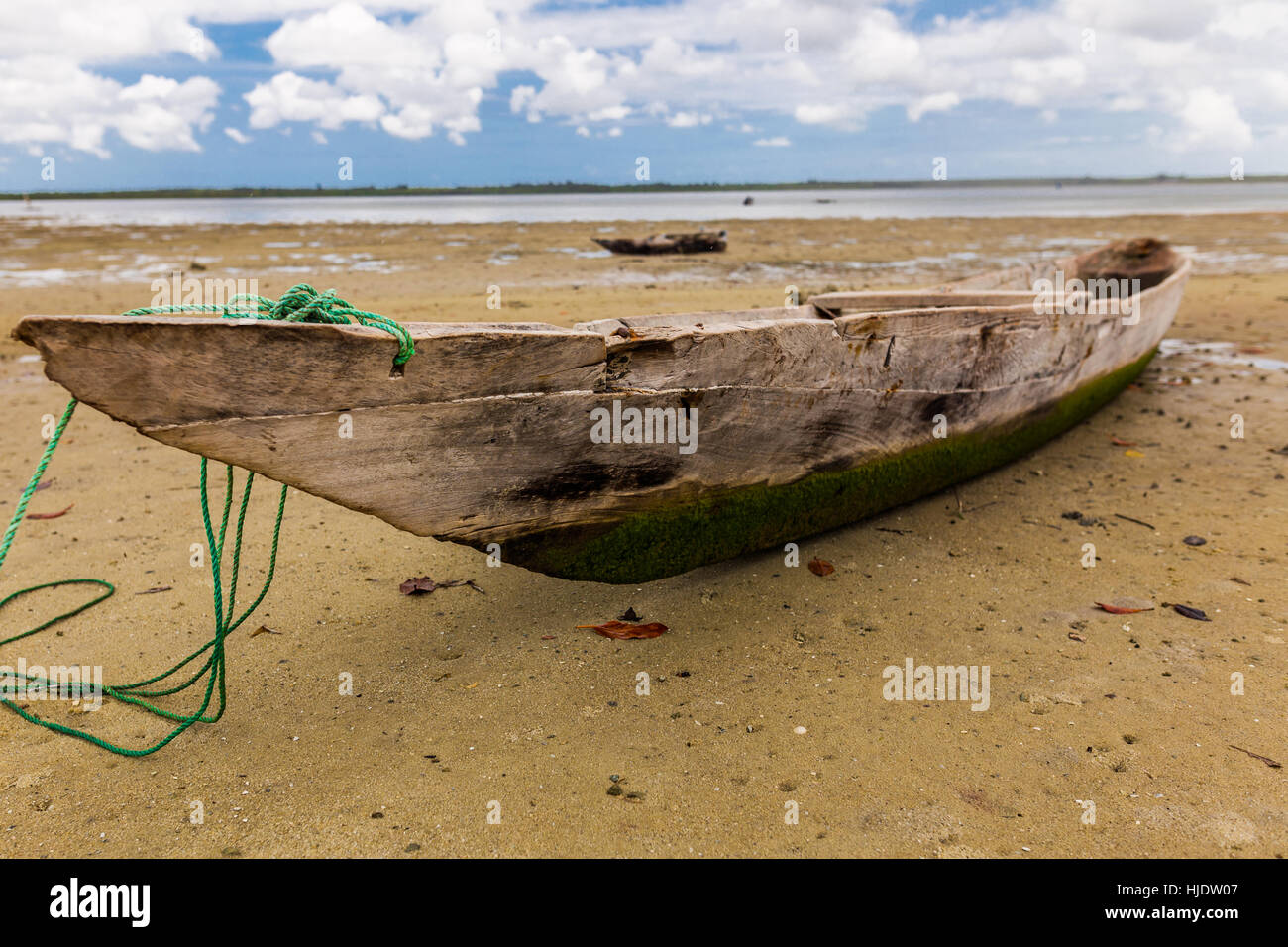 Native fisherman's simple wooden boat with green seaweed and blue sky in the background, Uzi Island, Zanzibar, - Stock Image
