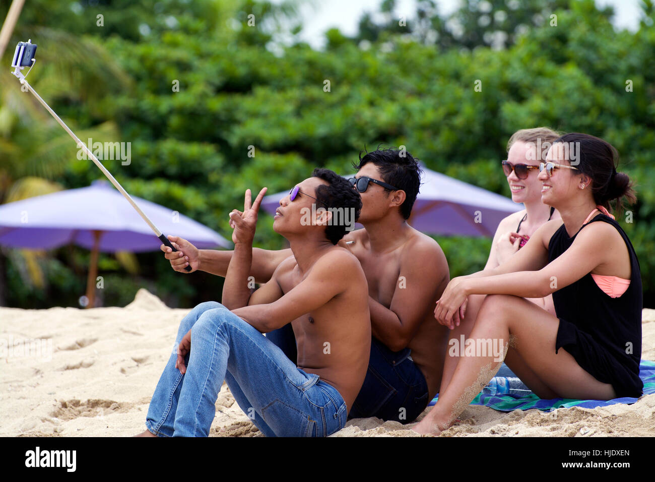 Friendly group of Young Balinese men pose for selfie photos with a couple of young western women. Peace Warm Wonderful - Stock Image