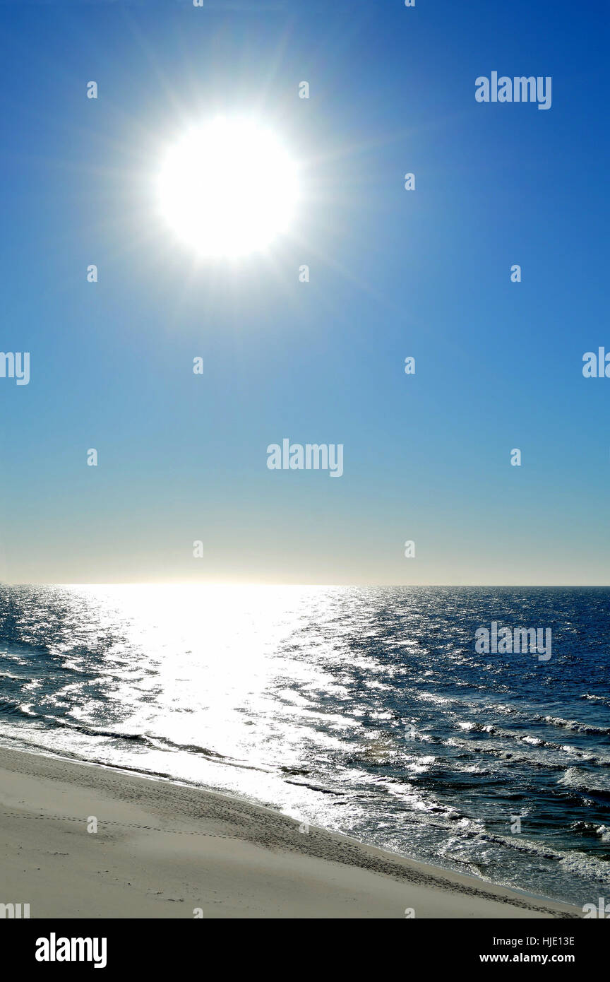 Sun glimmering on the ocean,white sand beach, and a bright blue sky. The sun is in the shape of an anvil at Perdido - Stock Image