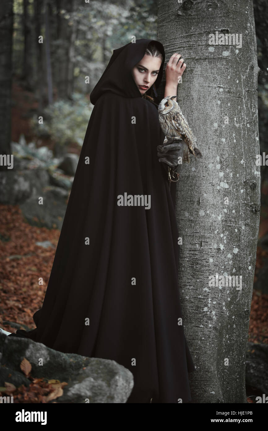 Forest keeper with black cloak and grey owl. Fantasy and legend - Stock Image