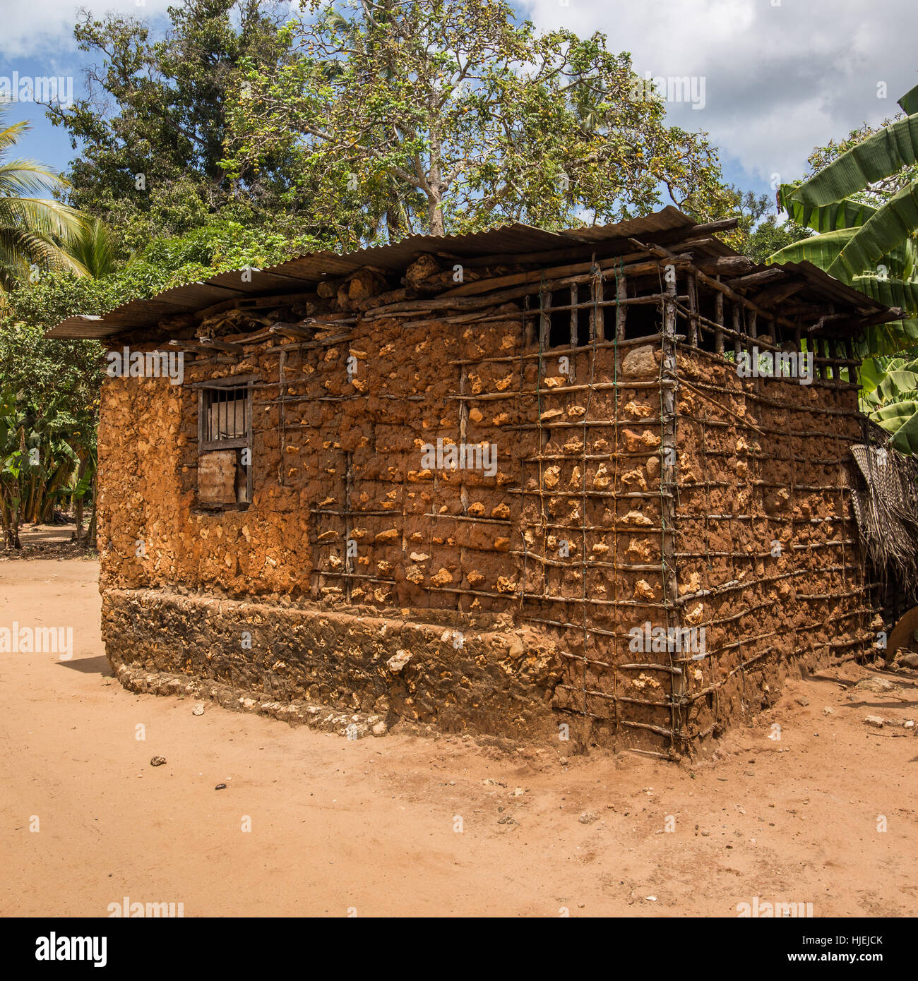 Small primitive house with steel sheet roof,built by native local people, made out of wooden sticks and red soil - Stock Image