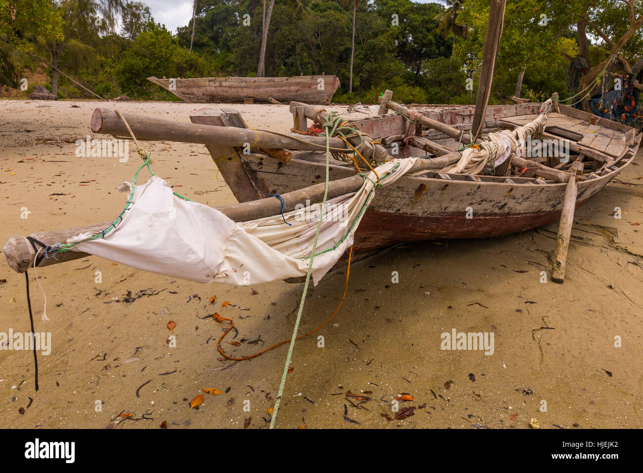 Big primitive fisherman wooden boat on beach with white sails and thin sailing masts made by native people, Uzi - Stock Image