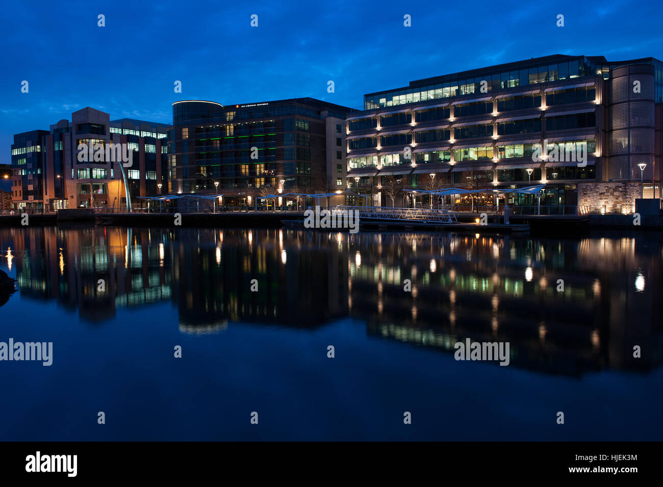 Clayton Hotel on Lapps Quay in Cork City at dusk which is part of the dockland rejuvenation reflected in the river - Stock Image