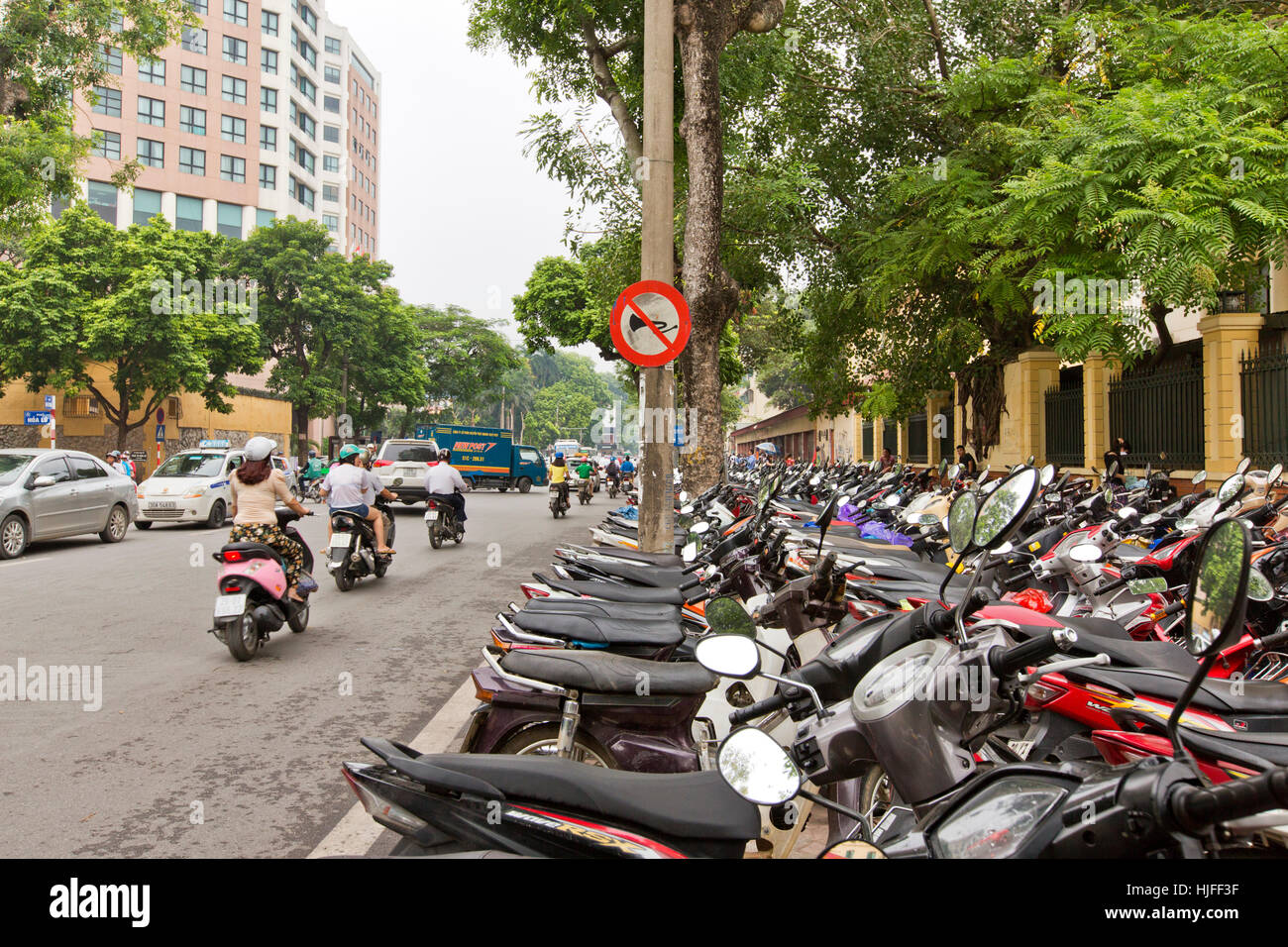 City street,  row of motorcycles & scooters parked on sidewalk. - Stock Image