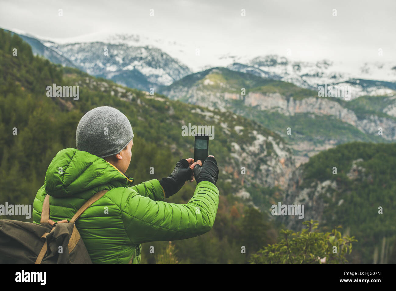 Young man traveller making photo of mountains, Alanya, Turkey - Stock Image