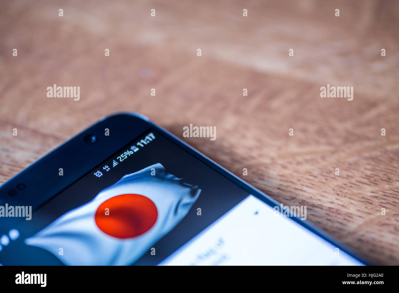 Smartphone on wooden background with 4G network sign 25 per cent charge and Japan flag on the screen. Stock Photo