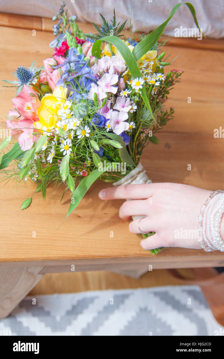 Bride,hand,bunch of flowers,wild flowers,flower,colorful,finger,bracelet,wedding,wedding day,most beautiful,day,in,life,marriage - Stock Image