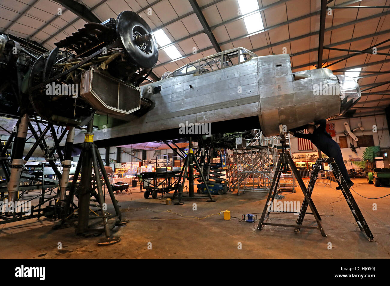 Roy Lemmon works on the Avro Lancaster NX611 'Just Jane' as restoration works continue on the aircraft at - Stock Image