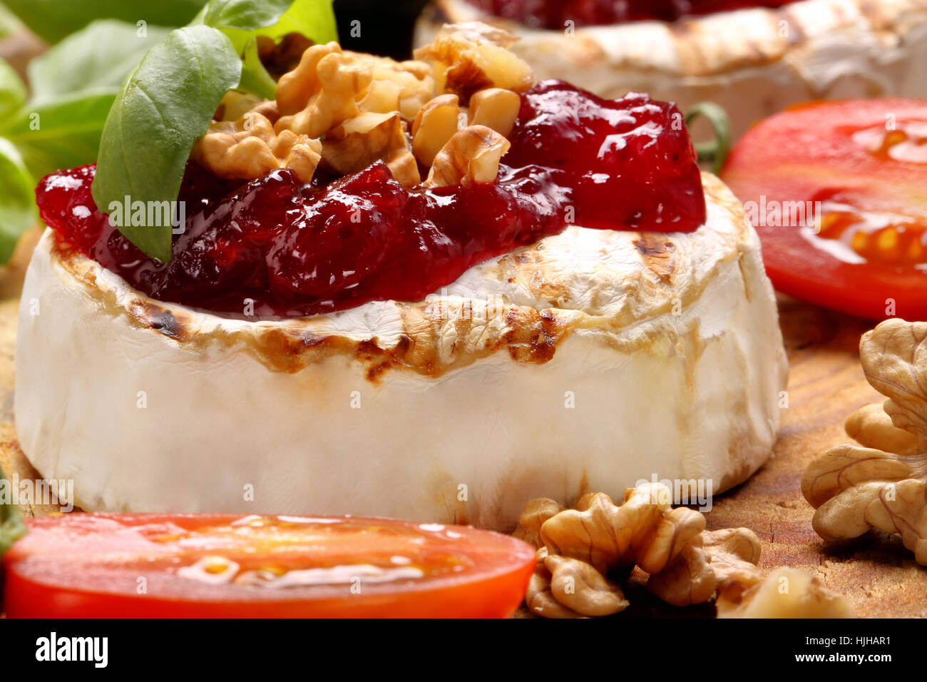 Grilled brie cheese with cranberry jam and walnuts on old wooden background - Stock Image