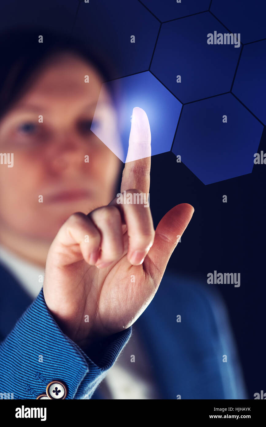 Businesswoman working in futuristic cyberspace hightech environment, hand pushing interface button - Stock Image
