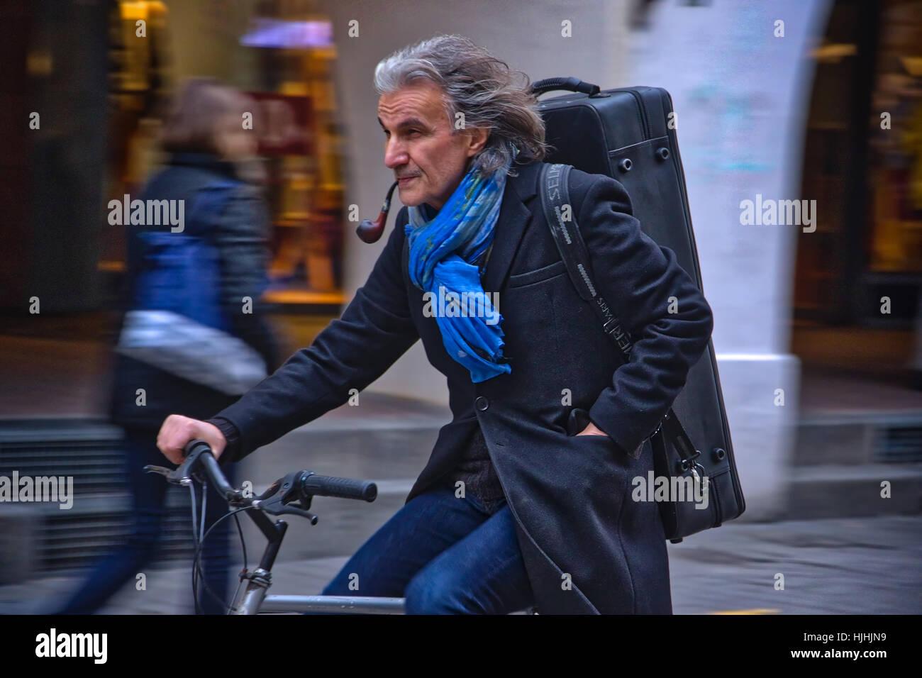 Man riding bike Smoking a pipe - Stock Image