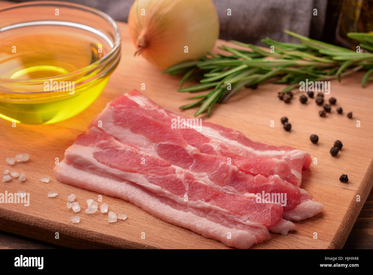 Still life with sliced raw bacon, olive oil, spices and herbs - Stock Image