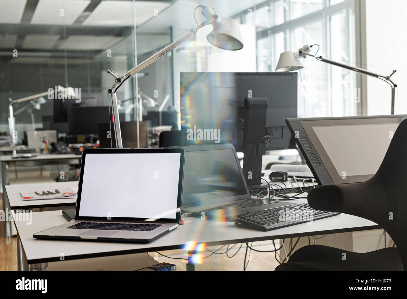 Computers on desk in office - Stock Image