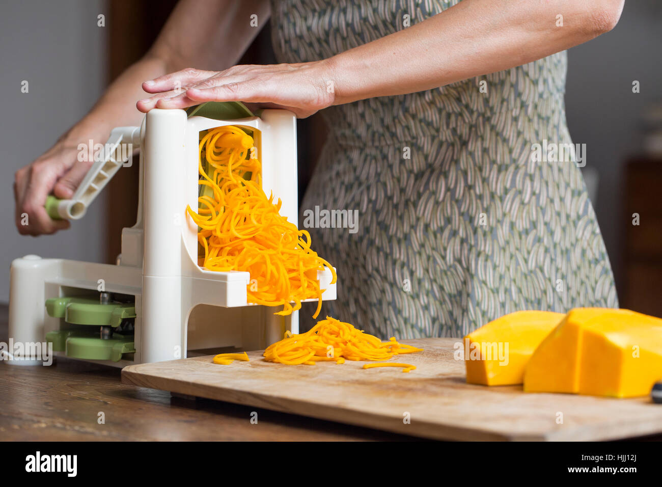Woman preaparing pumpkin noodles in spiral vegetable slicer Stock Photo