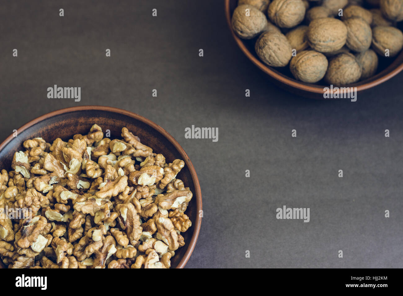 Walnut kernels and whole walnuts in brown ceramic bowls. Healthy organic food concept. - Stock Image