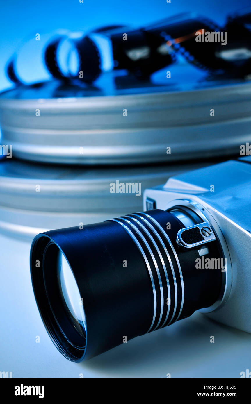 closeup of a retro film camera, some film strips and some metal movie film reel canisters on a table with, a blue - Stock Image