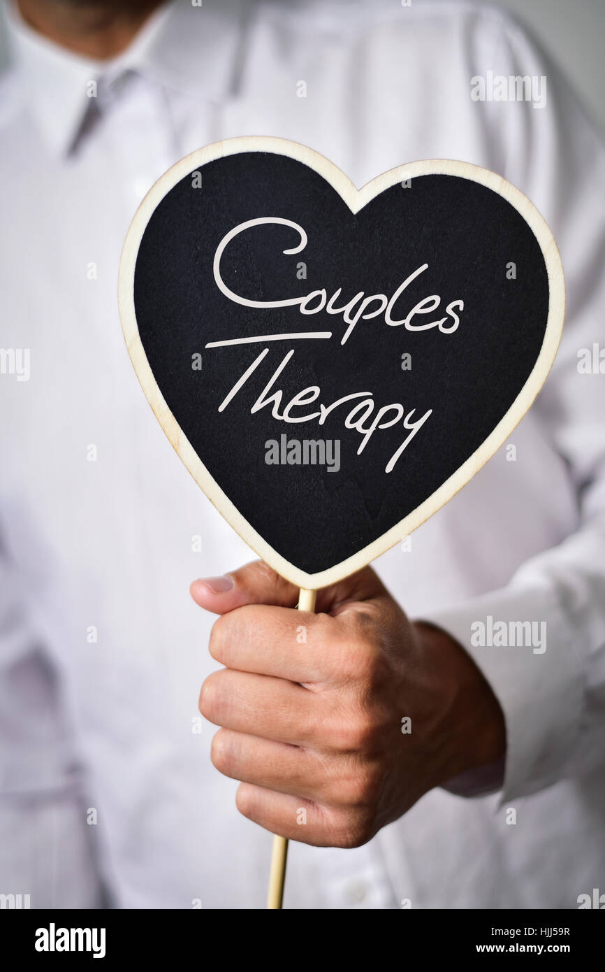 a young caucasian man wearing a white shirt shows a heart-shaped signboard with the text couples therapy written Stock Photo