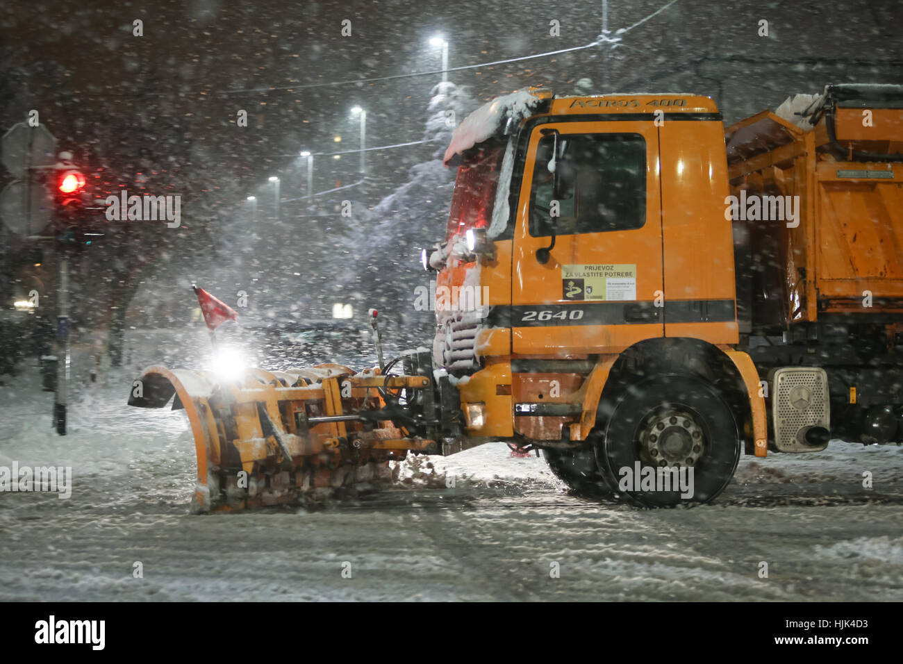 VELIKA GORICA, CROATIA - JANUARY 13th, 2017 : Snowplow cleaning streets in the aggravated traffic due to strong - Stock Image