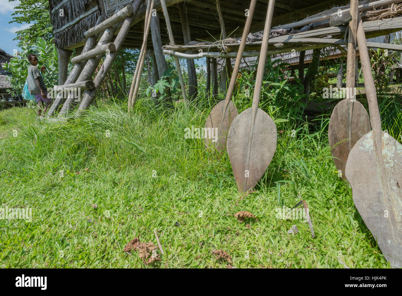 Young boy carrying a bag passing by a stilted house, with paddles in front, in a village on the Sepik River in Papua - Stock Image