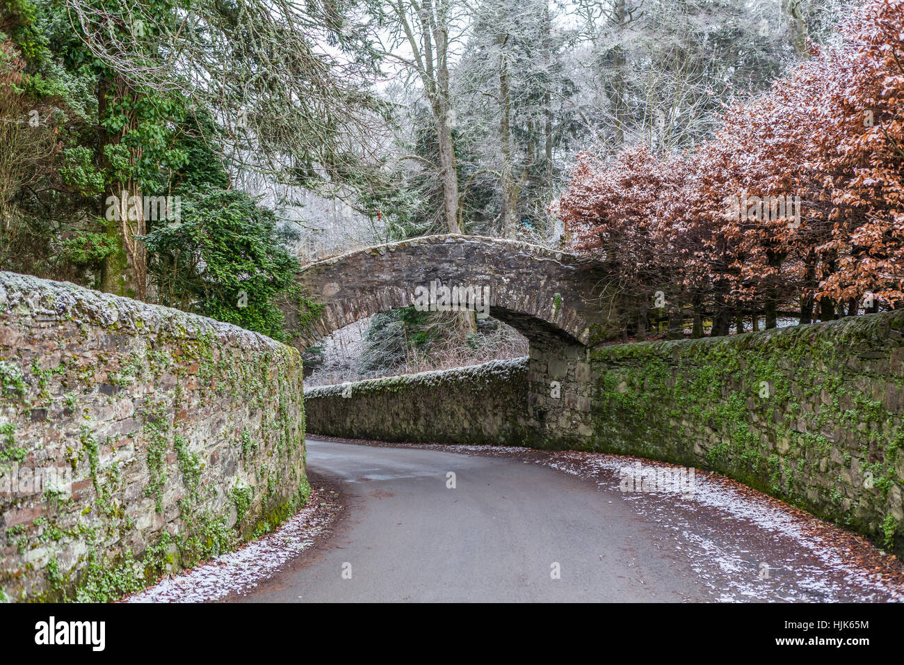 An old stone bridge crosses the road near Glen Tilt, Perthshire, Scotland, UK - Stock Image