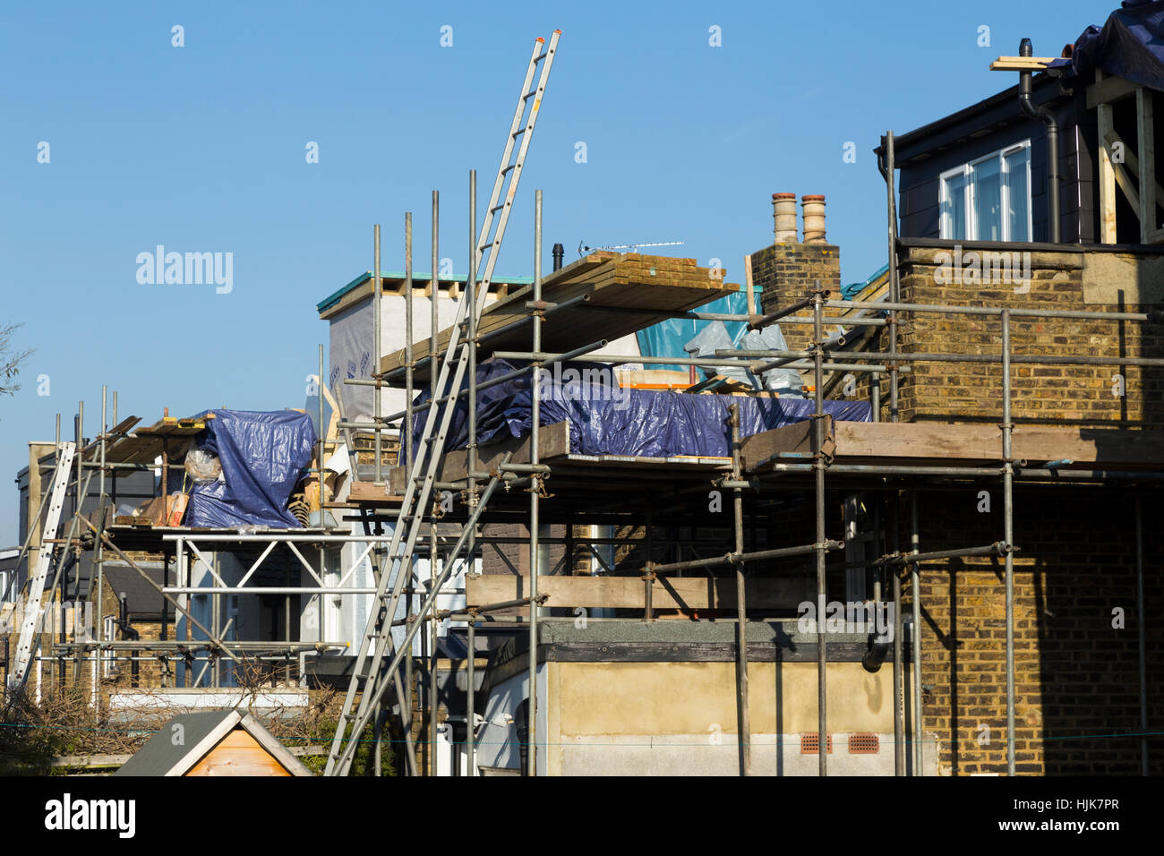 Scaffolding to a two new dormer / dormers / dormas / dorm on the roof / roofs of Victorian terraced house / houses. Stock Photo