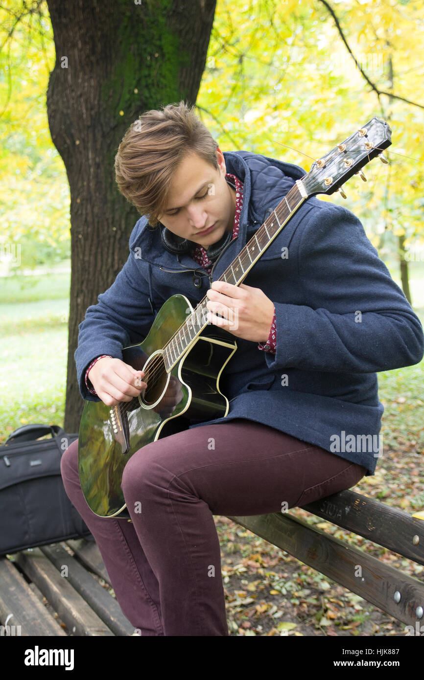 Young man with an acoustic guitar, Selective focus and small depth of field, lens flare Stock Photo