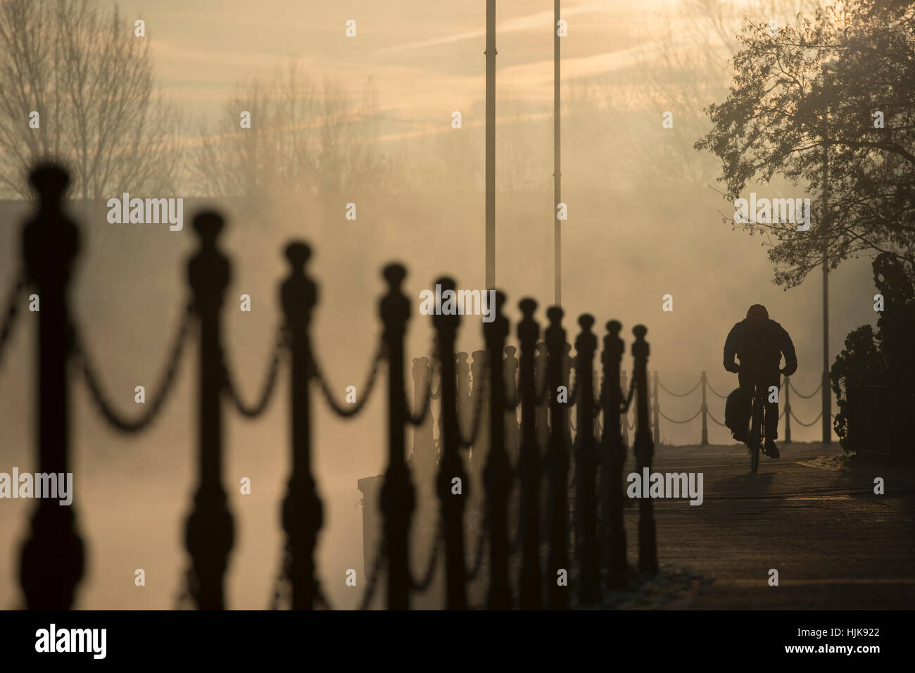 A person cycles along the towpath by River Lea, in Hackney, north London - Stock Image