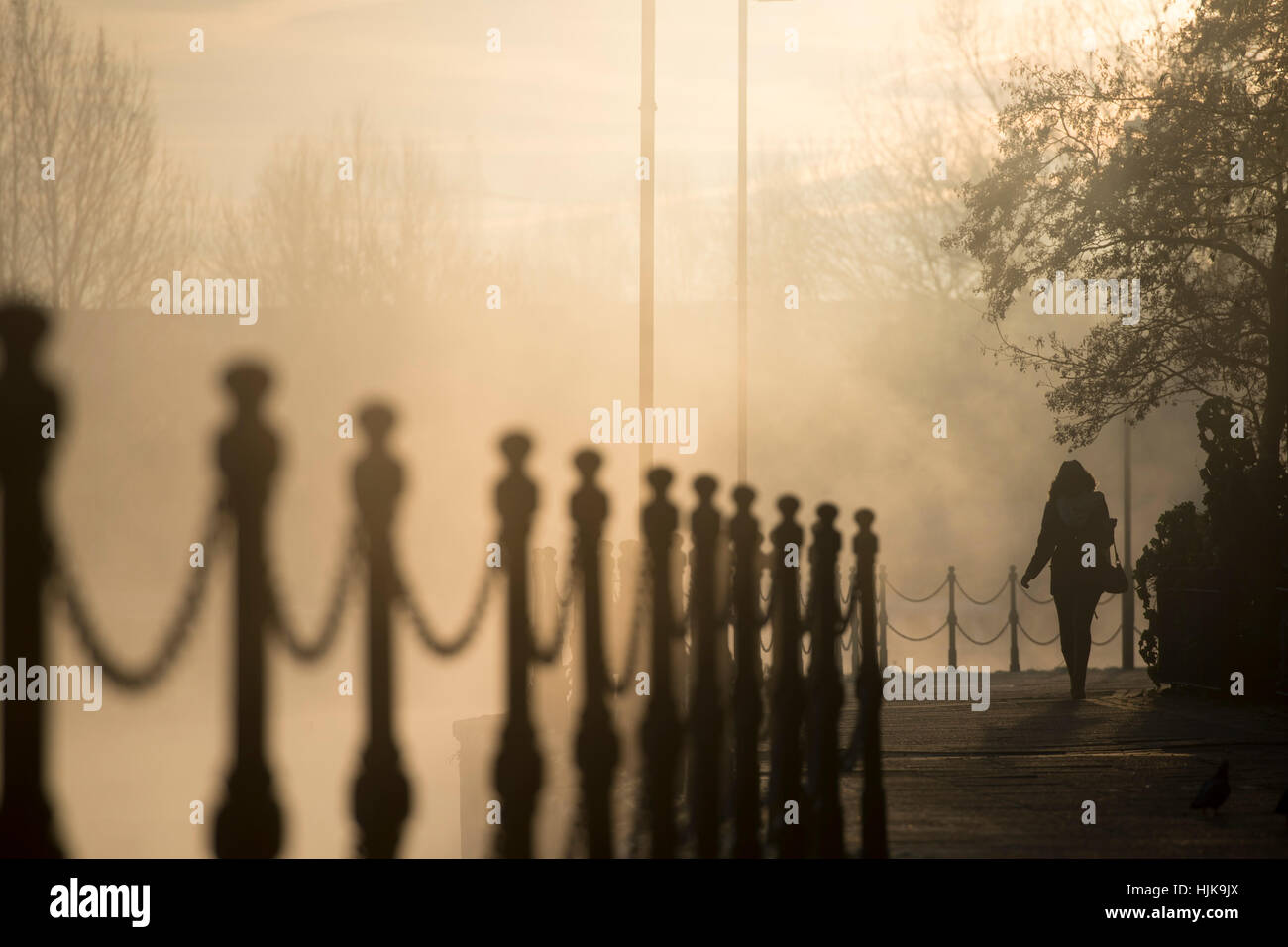 A person walks along the towpath at dawn, by the River Lea in London - Stock Image