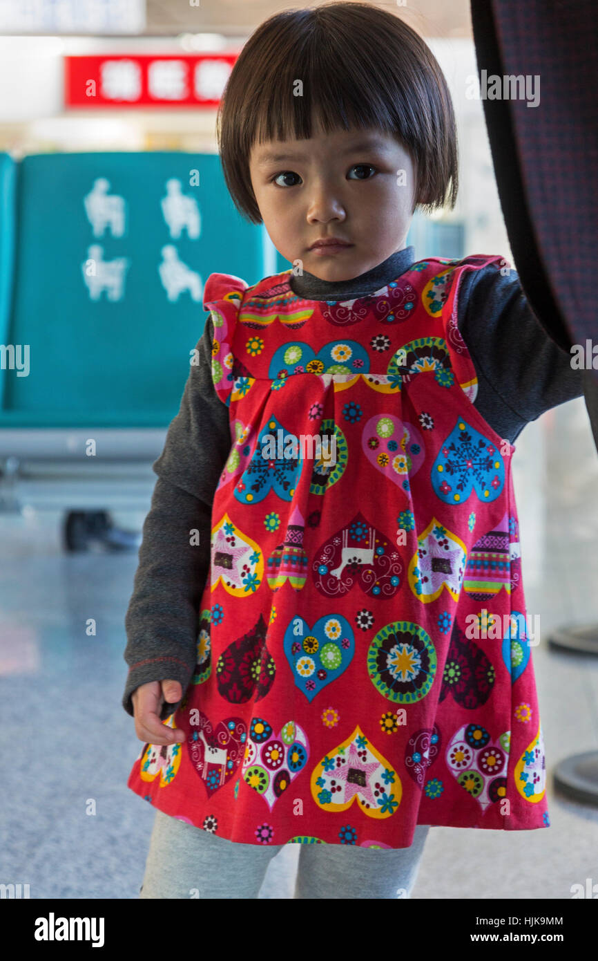 Young Chinese girl in smock, China - Stock Image