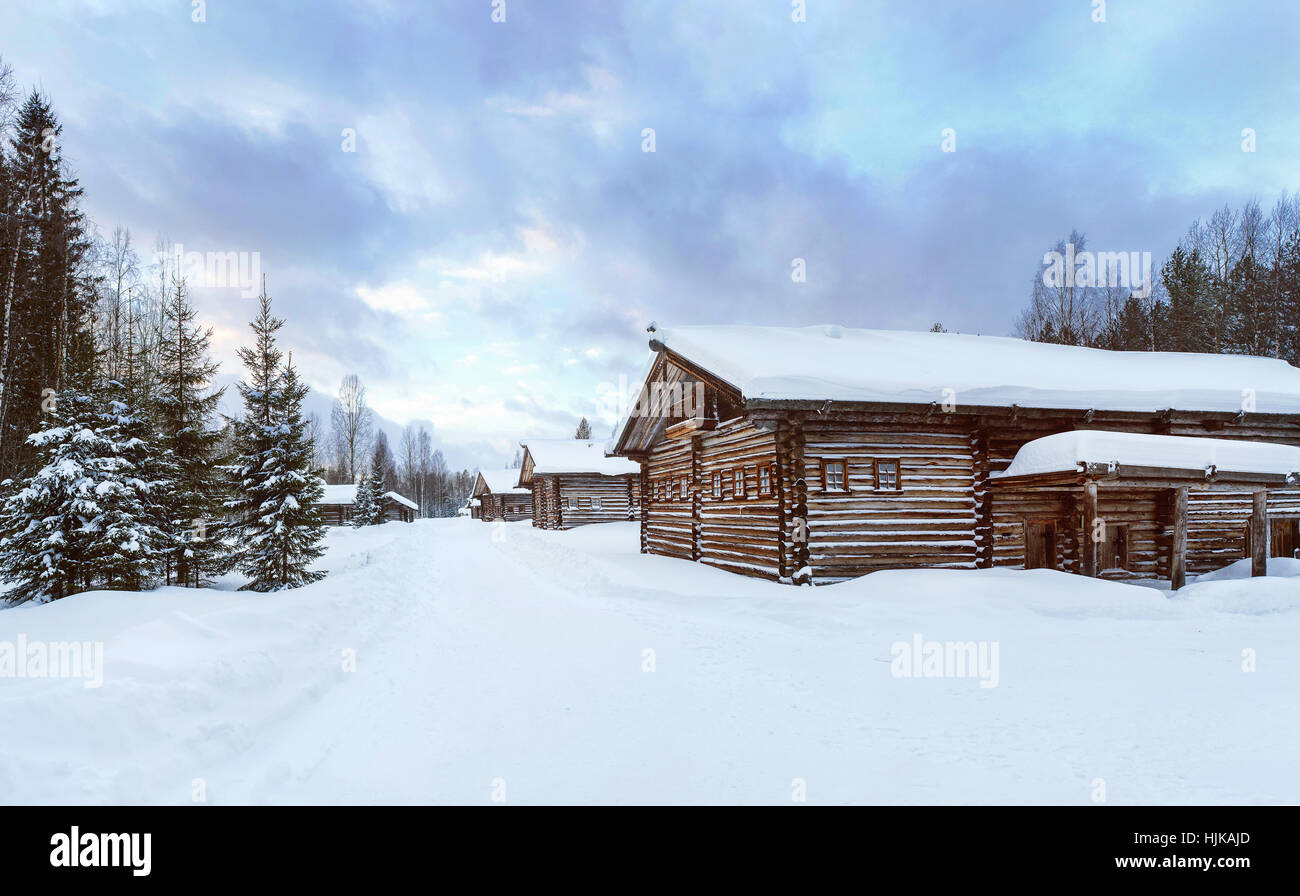 Old Village Log Houses in museum Small Karelians near Arkhangelsk, Russia. Winter sunset time. - Stock Image