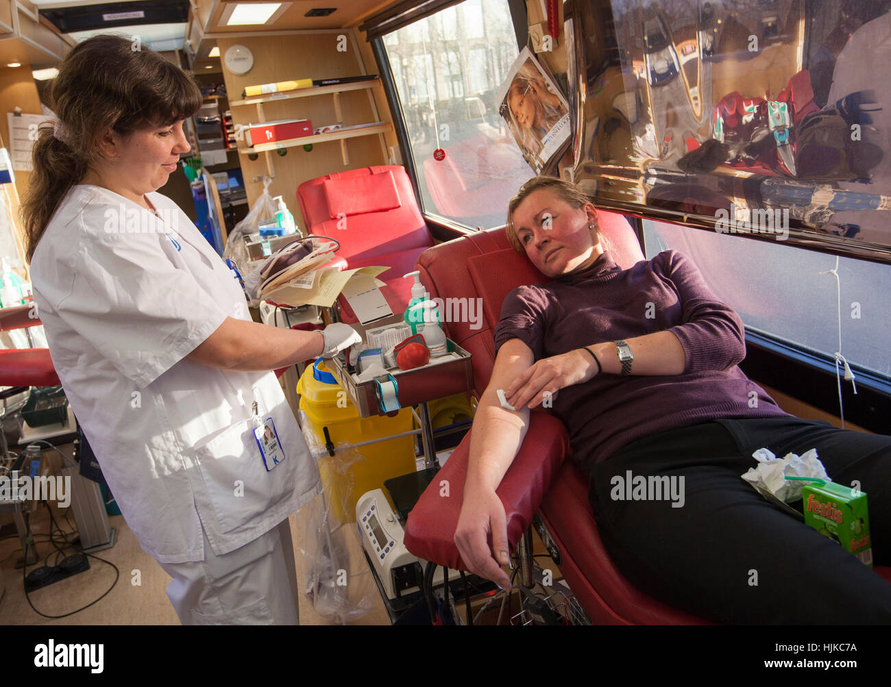 Blood donors visiting the blood bus to donate blood. - Stock Image