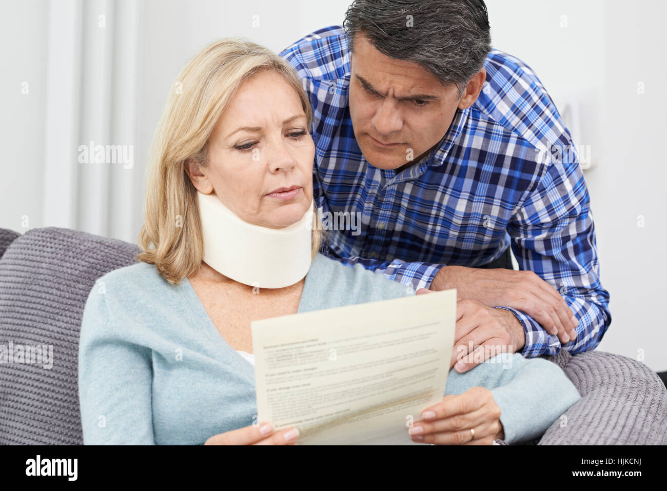 Couple Reading Letter About Woman's Injury - Stock Image