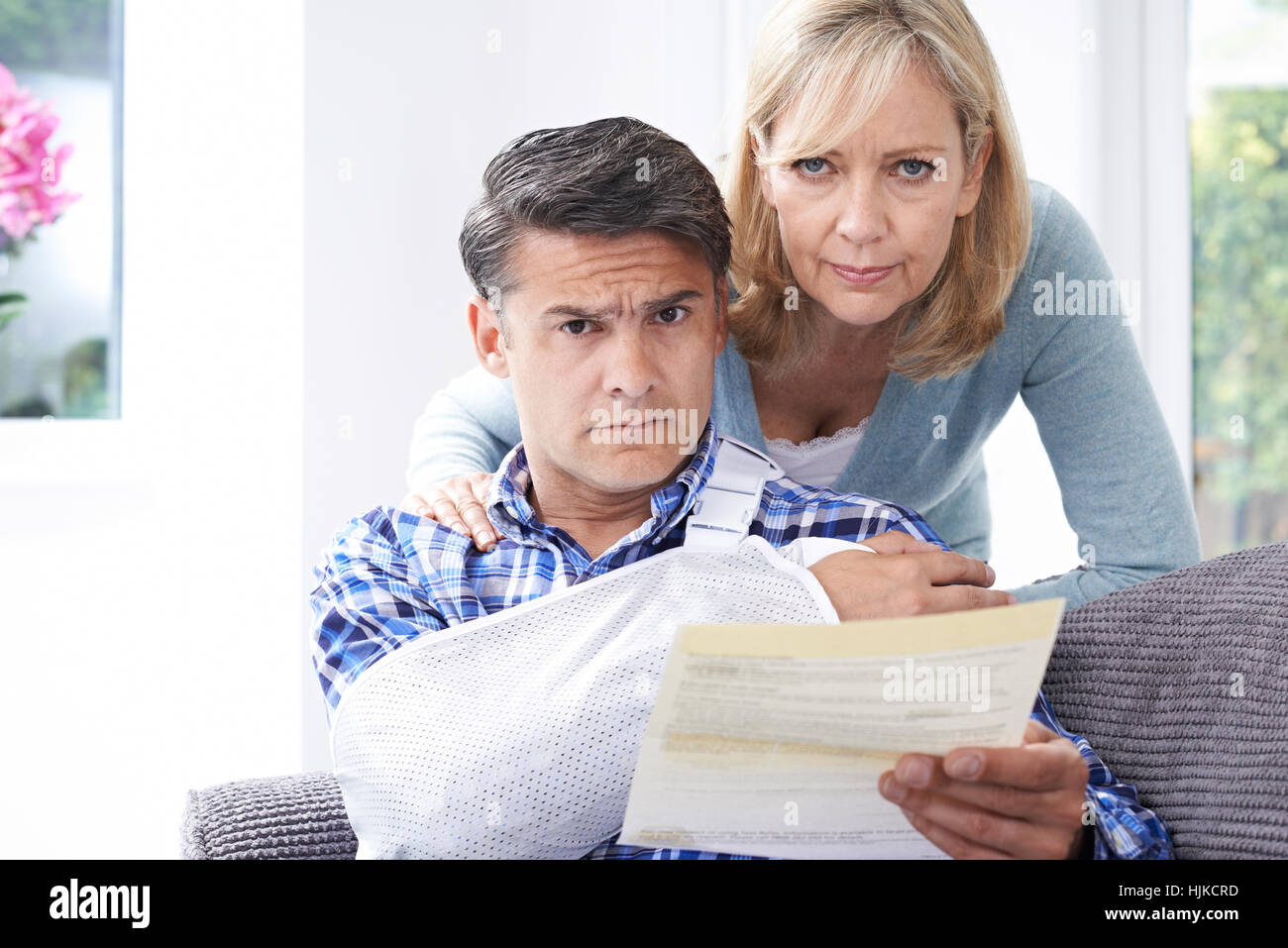 Couple Reading Letter About Man's Injury - Stock Image