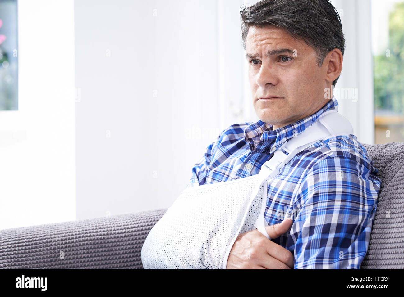 Mature Man With Arm In Sling At Home - Stock Image
