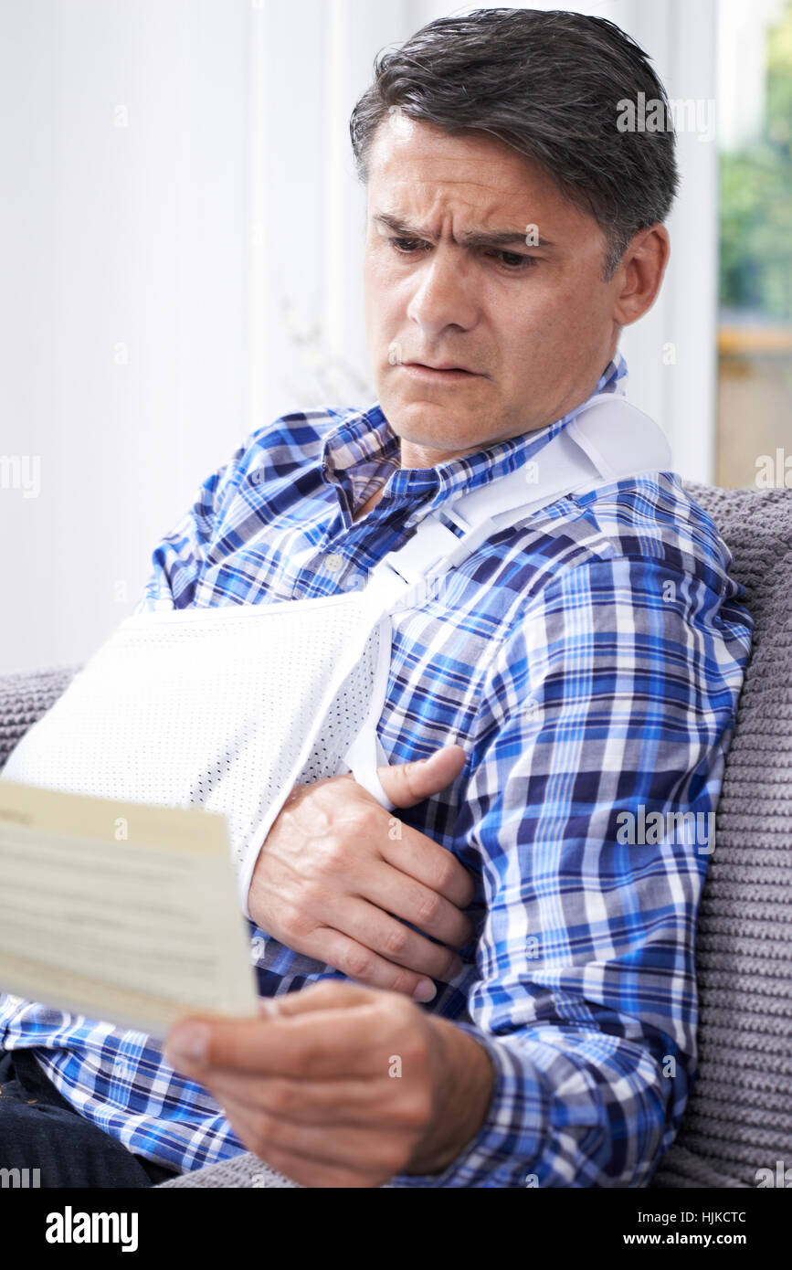 Mature Man Reading Letter About Injury - Stock Image