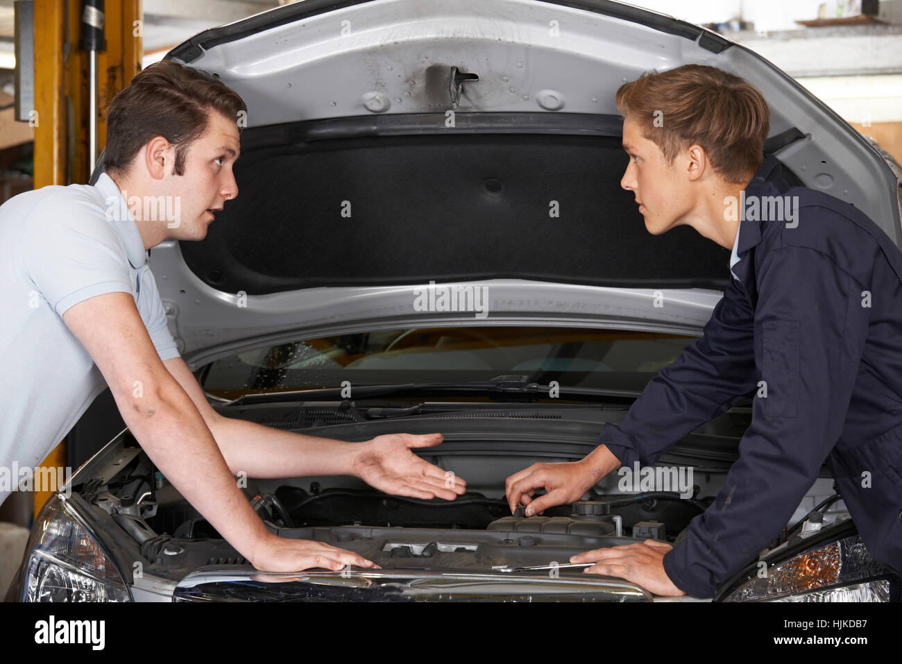 Mechanic Helping Apprentice To Fix Engine - Stock Image
