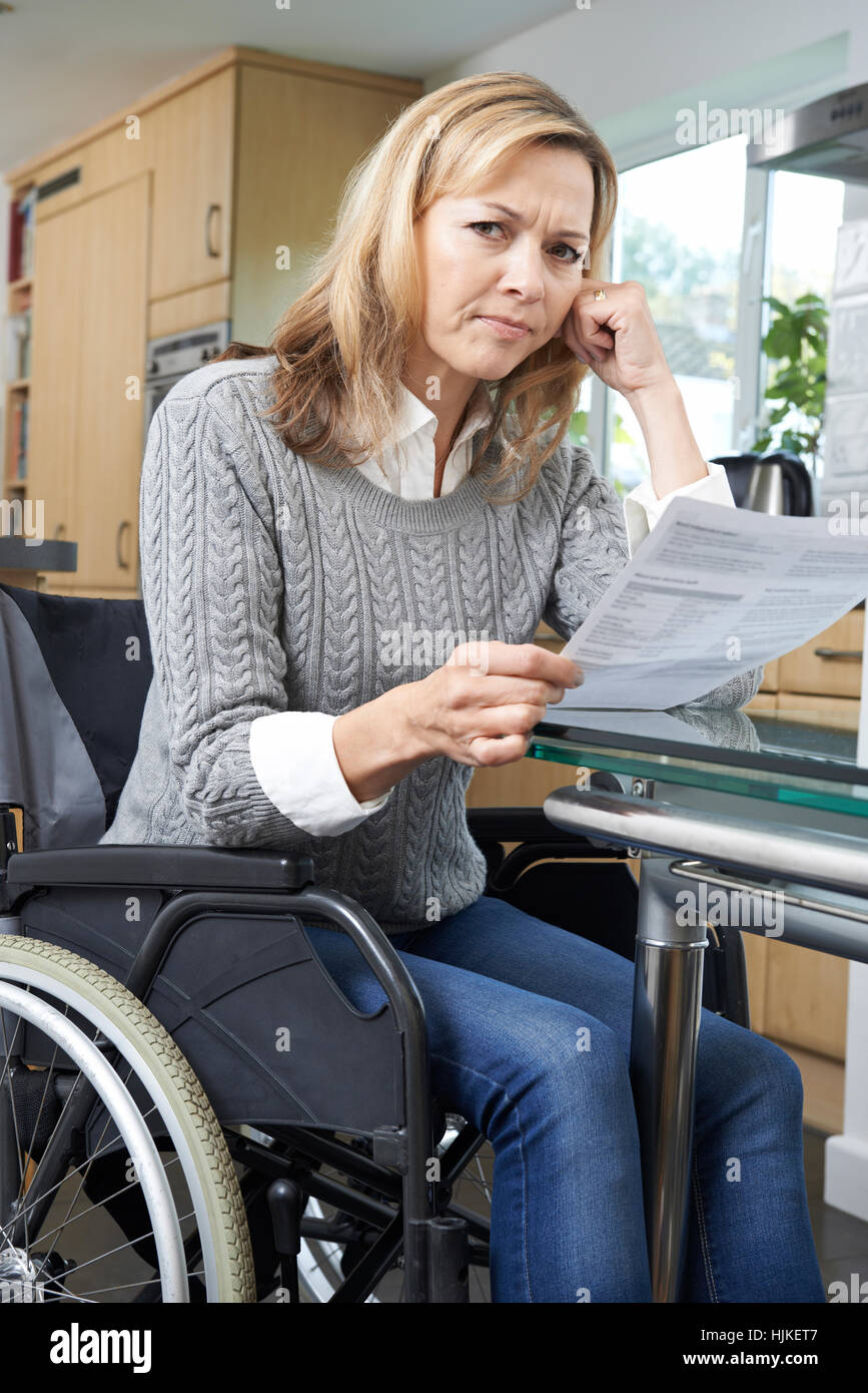 Frustrated Woman In Wheelchair Reading Letter - Stock Image