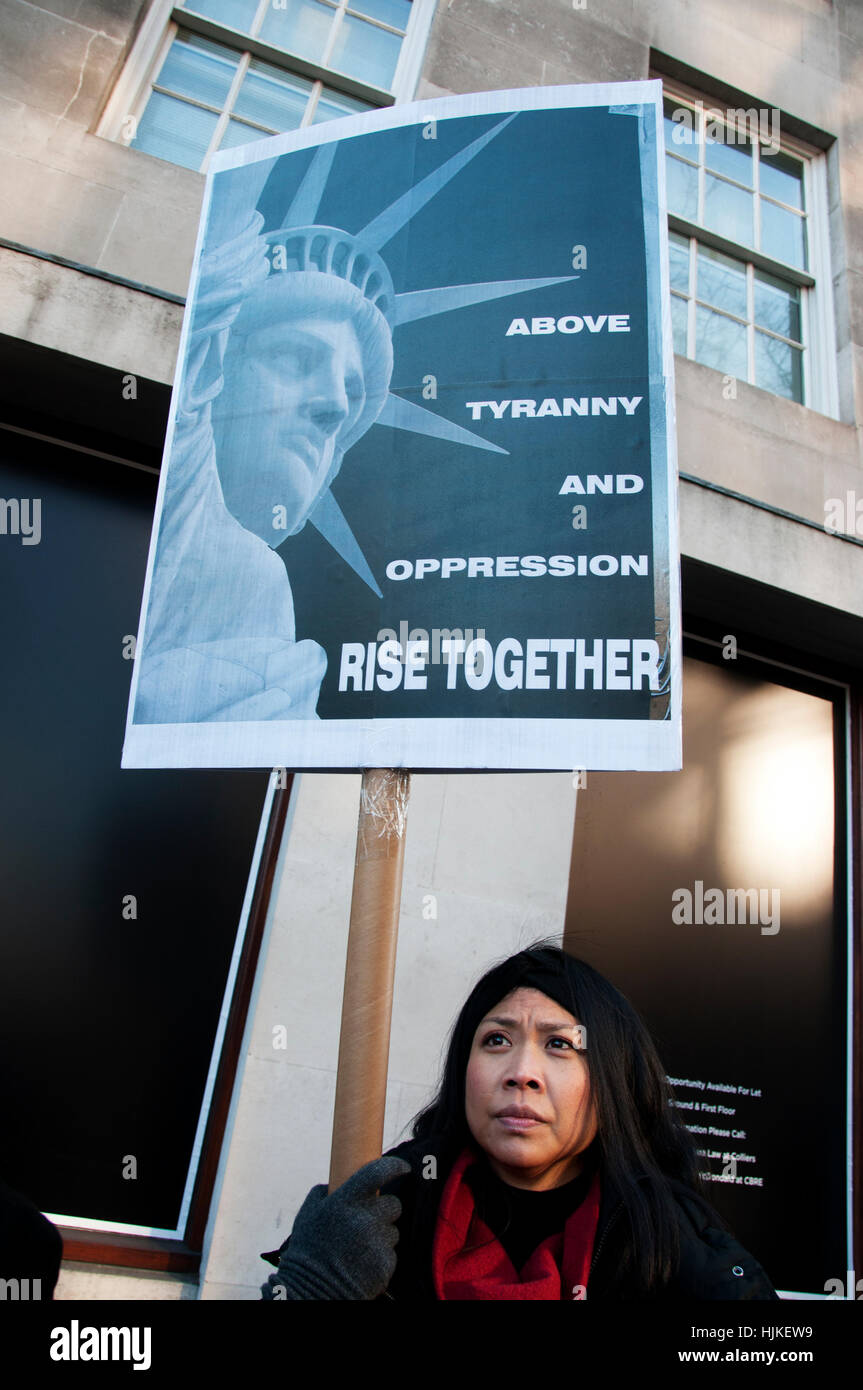 Women's march. A woman holds a placard of the Statue of Liberty and the words 'Above tyranny and oppression - Stock Image