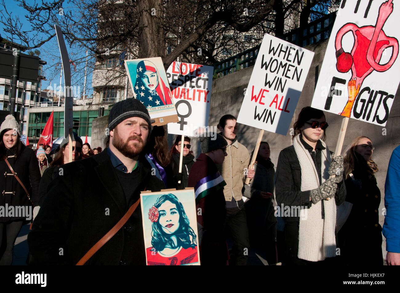 Anti-Trump Women's march. protesters carry posters by Shephard Fairey and placards supporting women - Stock Image